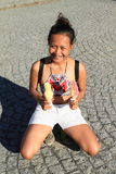 Girl holding ice-creams. Tropical girl - smiling Papuan woman holding two big yellow and pink ice-creams on stone pavement Stock Image