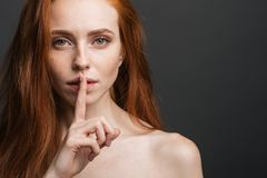 Girl holding index finger at her lips, saying `shh`. Redhead girl with freckles holding index finger at her lips, quiet and shh gesture royalty free stock photos