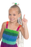 Girl holding index finger up. Girl draws attention holding up her index finger. Girl is six years old royalty free stock photography