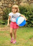 Girl holding inflating ball Royalty Free Stock Image