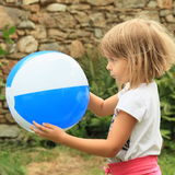 Girl holding inflating ball Stock Images