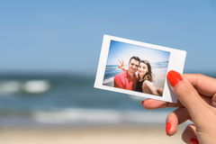 Girl Holding Instant Photo Of Happy Couple Stock Photo