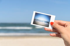 Girl Holding Instant Photo Of Sea Beach Stock Images