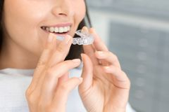 Free Girl Holding Invisible Braces, Moder Teeth Trainer Stock Photography - 161205352
