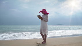 Girl are holding the ipad and stay on the beach. In the sunlight stock video footage