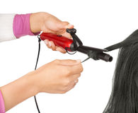 Girl holding iron curling hair Stock Image