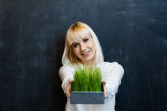 Girl, holding an iron pot with green grass on a dark background Royalty Free Stock Photos