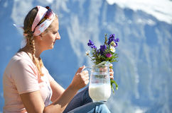 Girl holding a jug of milk and flowers Stock Photo