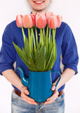 Girl holding jug with tulips Royalty Free Stock Photography