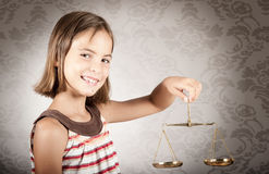 Girl holding justice scale. Little girl holding justice scale Royalty Free Stock Photo