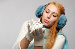 Girl holding and kissing a big snowflake. Royalty Free Stock Photography