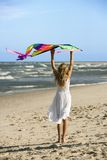 Girl holding kite on beach. Royalty Free Stock Photos