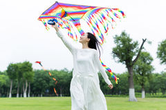 Girl holding a kite. In the beautiful spring, cute chinese girl flying a kite in the park Royalty Free Stock Photos