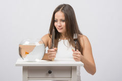 Girl holding knife and fork in hand and with an appetite for looking at the little goldfish Stock Photos