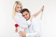 Girl holding knife traitor. man with rose in his hand. Royalty Free Stock Photography