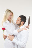 Girl holding knife traitor. man with rose in his hand. Girl holding knife traitor. men with rose in his hand. white background Stock Photos