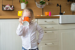 Girl holding a large cup of tea in the kitchen Stock Photos