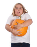 Girl Holding Large Pumpkin. A young girl holding a heavy and large pumpkin, isolated against a white background Royalty Free Stock Photography