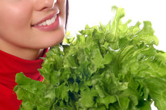 Girl is holding a leaf of salad Stock Photos