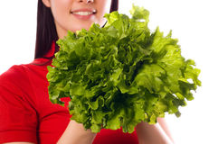 Girl is holding a leaf of salad. (isolated on white royalty free stock photos