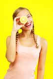 Girl holding lemons on yellow background Royalty Free Stock Image
