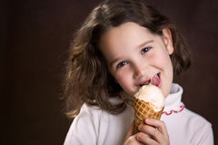 Girl holding and licking ice cream cone. Beautiful young girl licking an ice cream cone Royalty Free Stock Photos