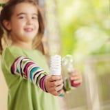 Girl holding light bulb Stock Photo