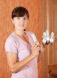 Girl holding light bulbs. Girl holding energy saving compact flourescent light bulbs royalty free stock photography