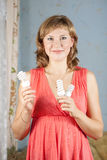 Girl holding light bulbs. Girl holding energy saving compact flourescent light bulbs royalty free stock photo