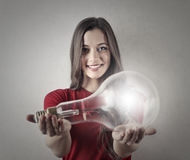 Girl holding a lightbulb Royalty Free Stock Images