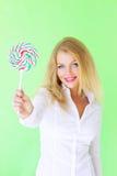 Girl holding lollipop. Beautiful girl holding lollipop on a light background stock photo