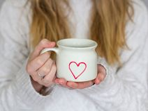 Girl Holding a Love Heart Coffee Cup. A mid section of a blonde haired girl wearing a cosy sweater and holding a tea cup with a love heart shape on in a royalty free stock photo