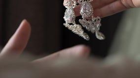 Girl holding luxury earrings. In her hands stock video