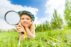 Girl holding magnifier lays alone on green grass Stock Photos