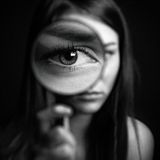 A girl holding a magnifying glass on a dark background, scary big eyes Stock Images