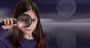 Girl holding magnifying glass on moonlight Royalty Free Stock Photo