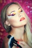Girl holding make up brushes Stock Image