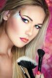 Girl holding make up brushes Stock Photography