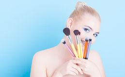 Girl holding make-up professional brushes and smiling Royalty Free Stock Photography