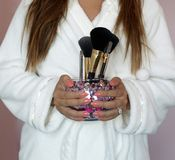 Girl holding makeup brushes Royalty Free Stock Image