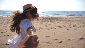 Girl holding male hand and running on beach to the ocean. Follow me shot of young woman in hat pull her boyfriend on the stock video