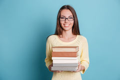 Girl holding many books over blue background Royalty Free Stock Photos