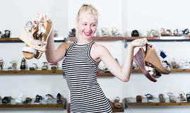 Girl holding many pair of shoes. Girl holding many pair of heeled shoes in fashion store stock photography