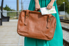 Girl in a holding a map and suitcase at station Royalty Free Stock Photo