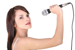 Girl holding microphone. Young girl singing into a microphone Royalty Free Stock Images