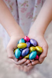 Girl holding mini chocolate coloured easter eggs Royalty Free Stock Photos