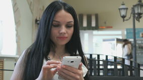 Girl holding a mobile phone in a cafe stock video footage