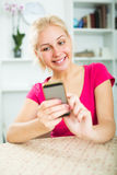 Girl holding mobile phone at home Stock Photo