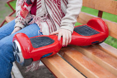 Girl holding modern red electric mini segway or hover board scooter Royalty Free Stock Photo
