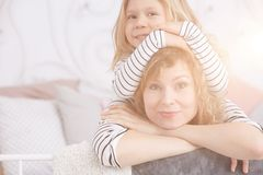 Girl holding mom`s head. Young little girl holding her mom`s head royalty free stock photography